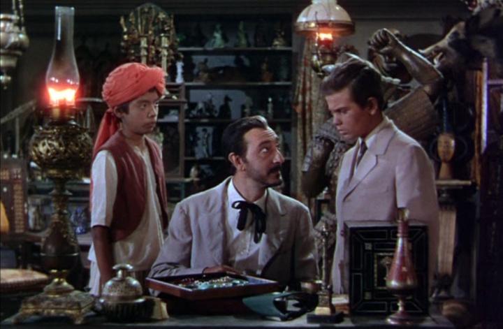 Fotograma de la versión cinematográfica de 1950. Kim (un jovencísimo Dean Stockwell) afronta los desafíos a que le somete el misterioso sahib Lurgan (Arnold Moss).
