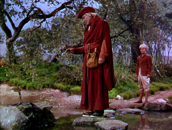 Fotograma de la versión cinematográfica de 1950. El lama (Paul Lukas) habla con alguien que se reencarnó en serpiente, ante la mirada de Kim.